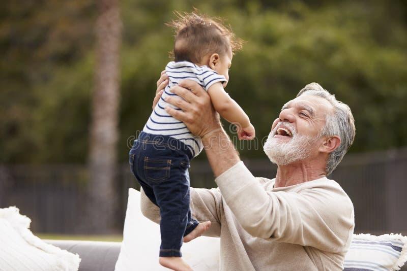 Homem latino-americano superior que senta-se no jardim que levanta seu neto do bebê no ar e que sorri a ele foto de stock