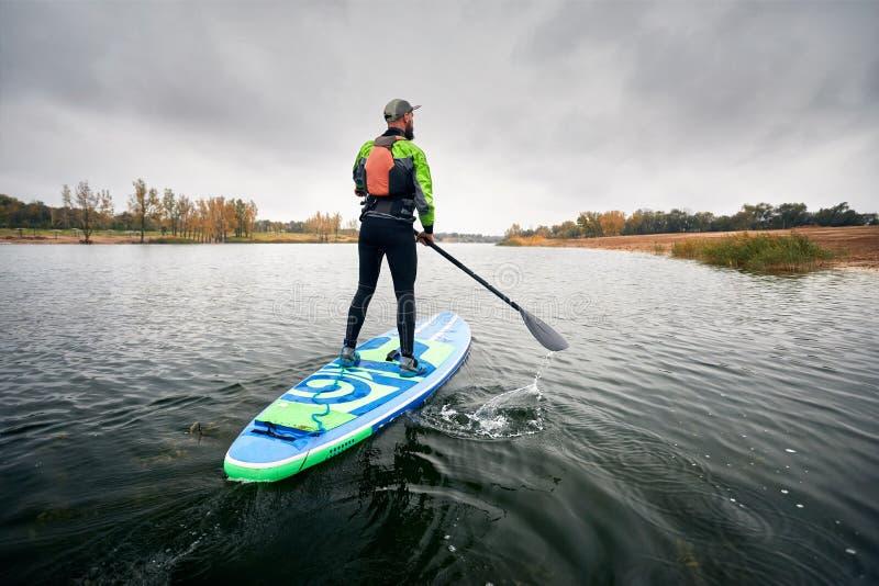 Homem levantar-se no paddleboard imagem de stock