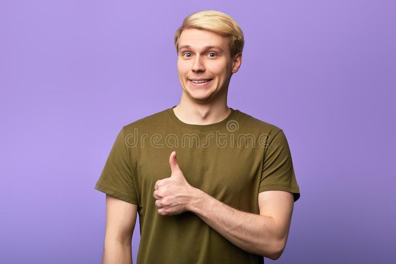 Homem lindo de sorriso com o polegar acima do levantamento à câmera fotografia de stock royalty free