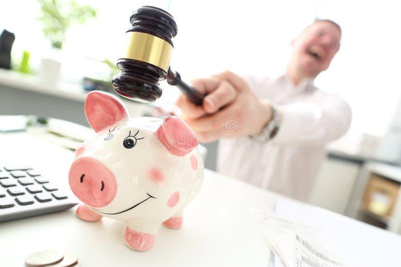 Homem louco com o malho que tenta quebrar o piggybank engraçado fotos de stock royalty free