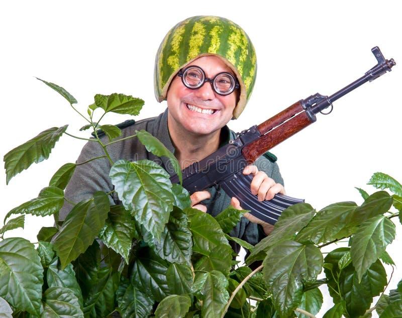 Homem louco em um capacete da melancia que patrulha com arma imagens de stock