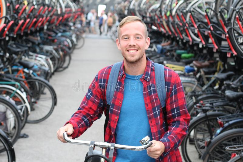 Homem louro alegre no parque de estacionamento da bicicleta 3D imagem de stock