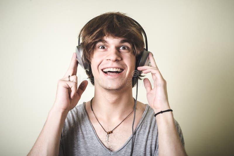Homem louro novo à moda do moderno que escuta a música imagem de stock
