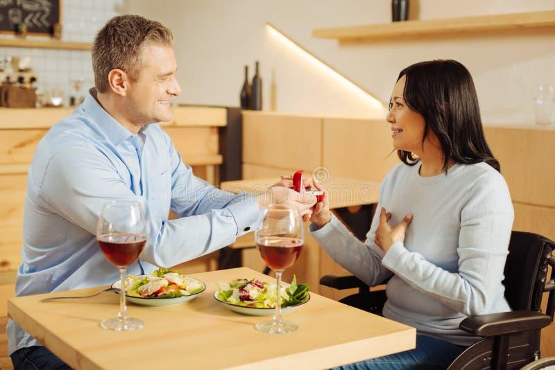 Homem loving que propõe a uma mulher deficiente imagem de stock