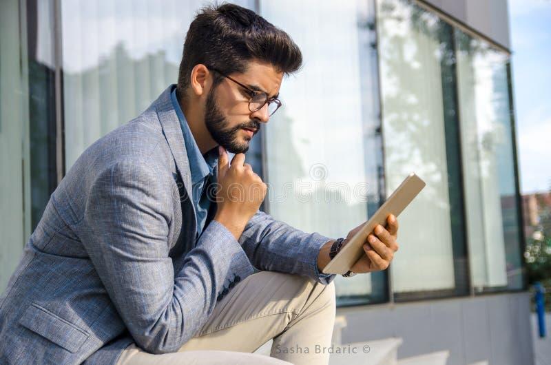 Homem macho considerável que senta-se em escadas na frente do prédio de escritórios moderno imagens de stock royalty free