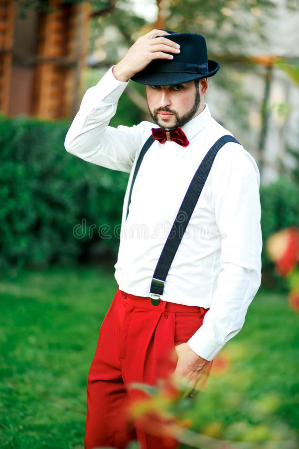 Homem macho em um chapéu e em uma calças vermelha com suspensórios imagens de stock