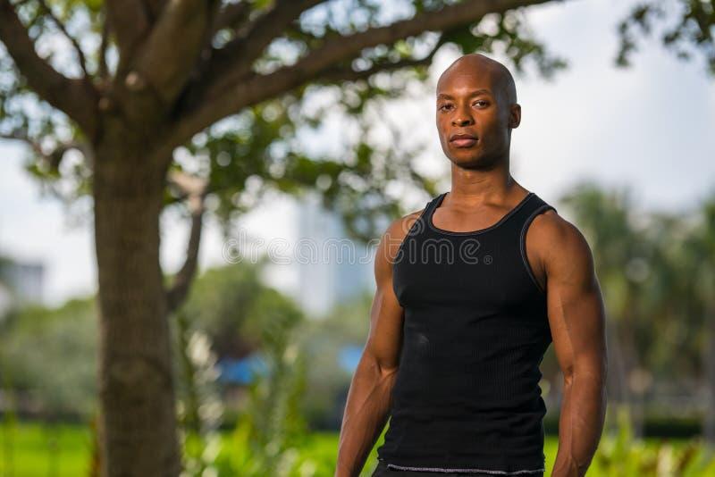 Homem macho que levanta em uma camisa da camiseta de alças imagens de stock