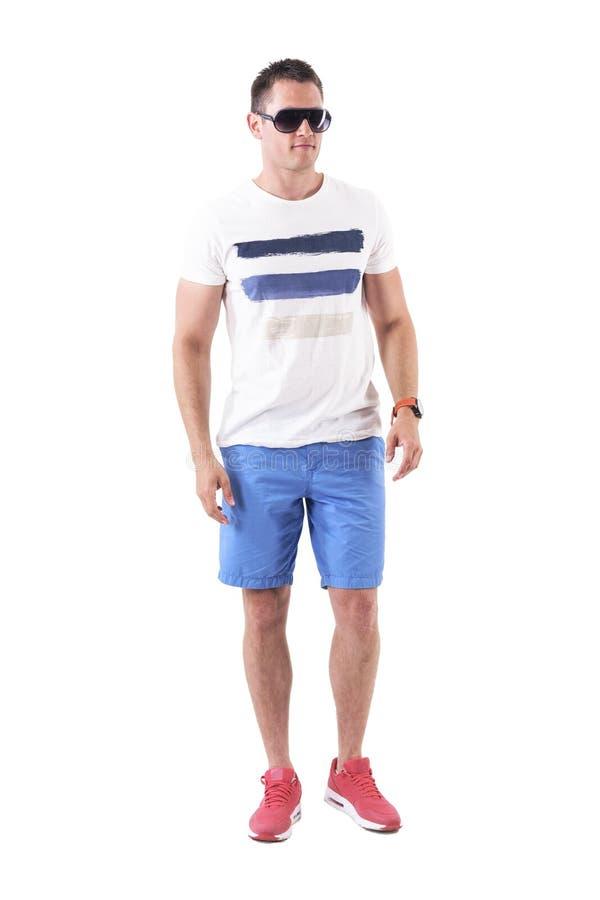 Homem macho sério seguro no short do verão com óculos de sol que anda para a frente imagem de stock royalty free