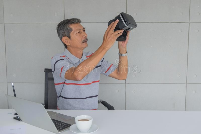 Homem maduro asiático, guardando vidros de VR para testar a tecnologia moderna nova fotografia de stock