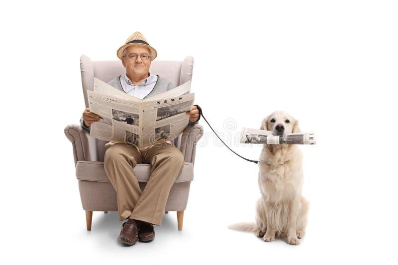 Homem maduro assentado em uma poltrona que guarda um jornal e um labra imagens de stock