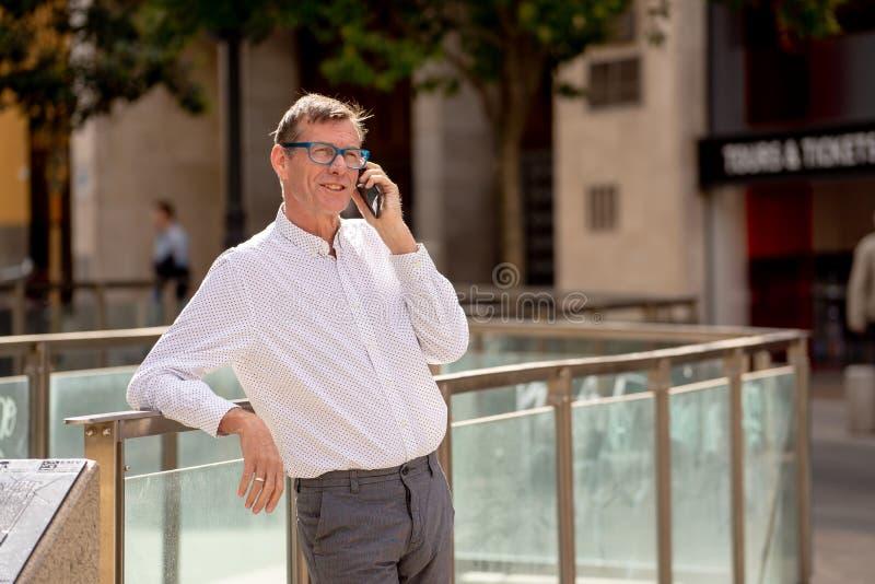 Homem maduro atrativo feliz em seu telefone esperto ao andar no sorriso da rua imagens de stock royalty free