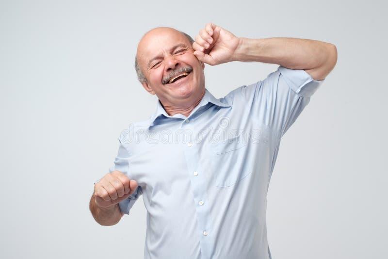 Homem maduro caucasiano com a cara sonolento que estica a tentativa para acordar fotografia de stock royalty free