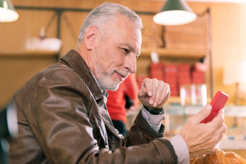 Homem maduro cinzento-de cabelo farpado que guarda seu smartphone vermelho foto de stock royalty free