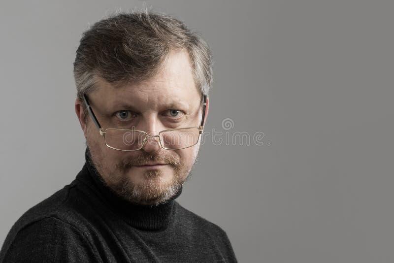Homem maduro com a barba no fundo cinzento imagem de stock