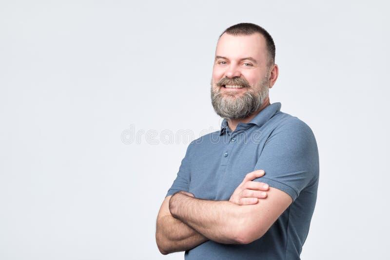 Homem maduro com a barba que mantém as mãos cruzadas e que olha a câmera ao sorrir imagens de stock royalty free