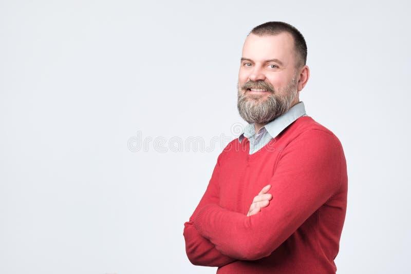 Homem maduro com a barba que mantém as mãos cruzadas e que olha a câmera ao sorrir imagem de stock