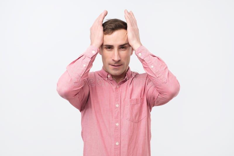 Homem maduro com a expressão histérica que guarda suas mãos na cabeça sobre o fundo branco foto de stock royalty free