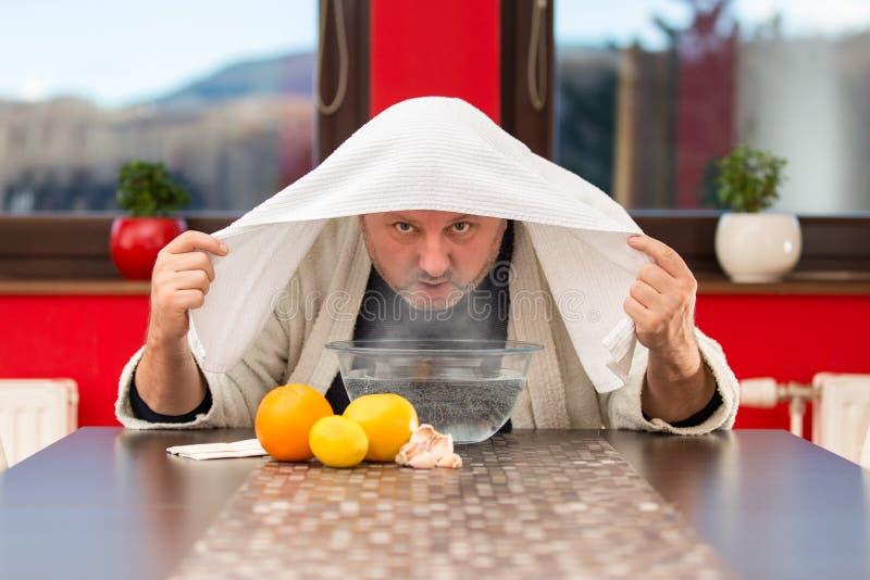 Homem maduro com frios e gripe Inalação das ervas imagem de stock