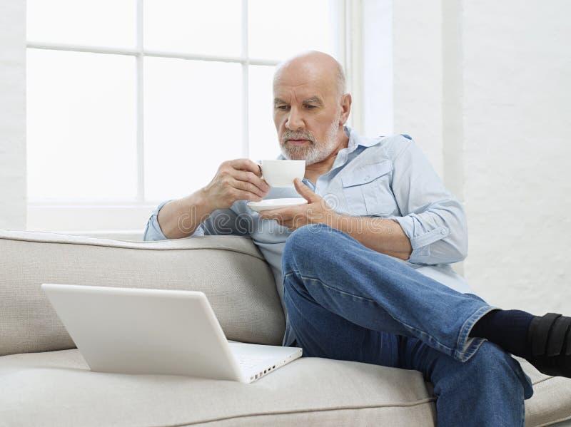 Homem maduro com o copo do portátil e de café no sofá fotos de stock royalty free