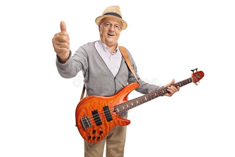 Homem maduro com um polegar da exibição da guitarra-baixo acima imagens de stock royalty free