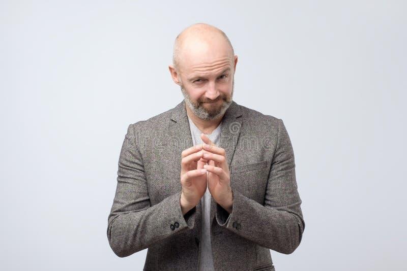 Homem maduro complicado astuto que pensa com mão junto sobre o fundo branco foto de stock royalty free