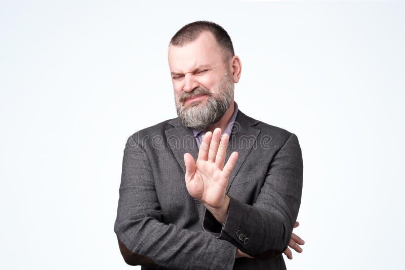 Homem maduro considerável com a barba que faz o sinal da parada fotos de stock