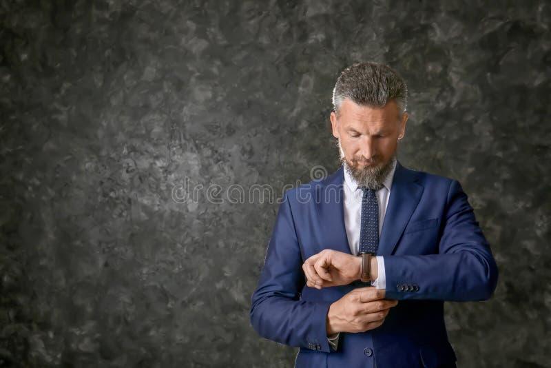 Homem maduro considerável no relógio de pulso vestindo do terno elegante no fundo textured escuro fotografia de stock