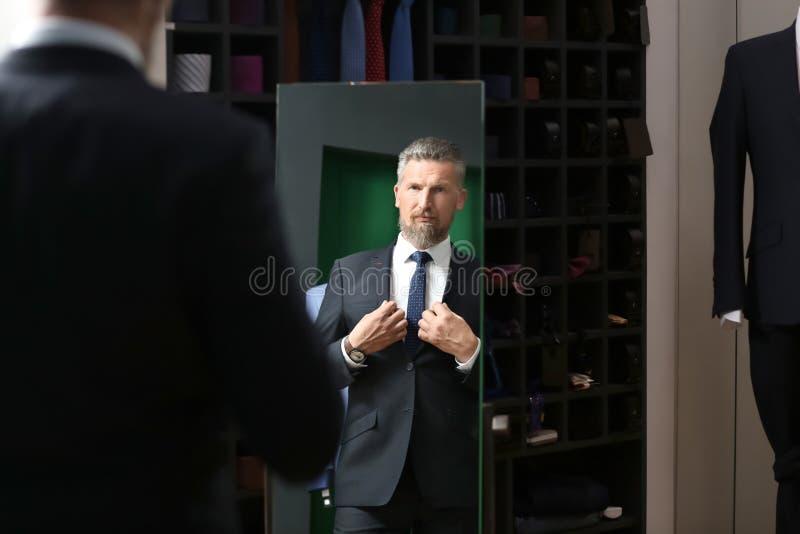 Homem maduro considerável que olha no espelho ao tentar no terno novo na loja fotografia de stock royalty free