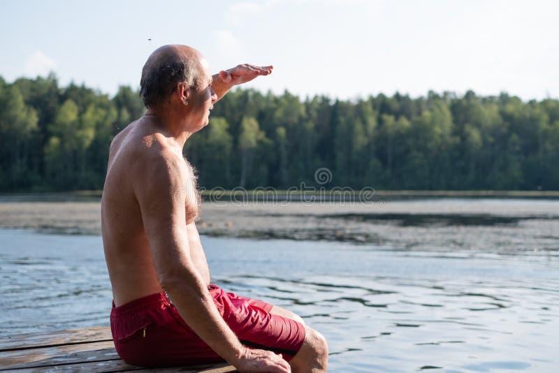 Homem maduro considerável que senta-se em um lago em um dia ensolarado, calmo, sentando-se em um cais de madeira imagem de stock royalty free