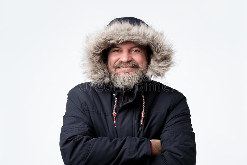 Homem maduro consider?vel que veste o Parka morno e a capa do inverno, sorrindo imagem de stock