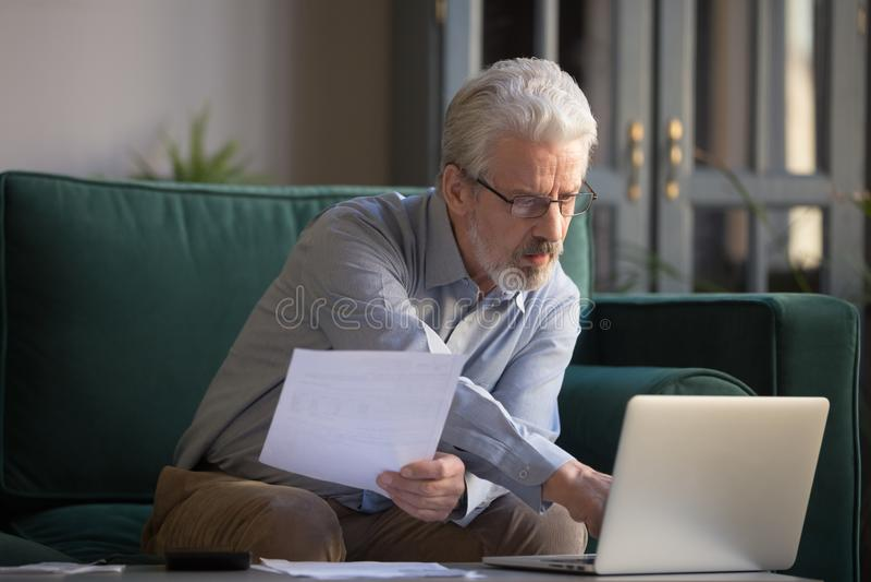 Homem maduro de cabelo cinzento que calcula contas, usando o portátil em casa foto de stock royalty free