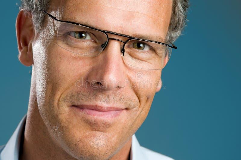 Homem maduro de sorriso com vidros fotografia de stock