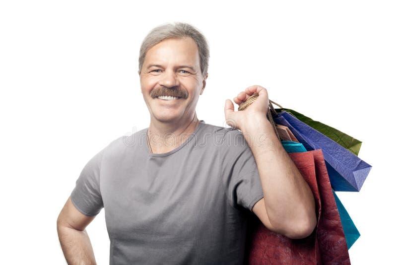 Homem maduro de sorriso que mantem sacos de compras isolados no branco imagens de stock royalty free