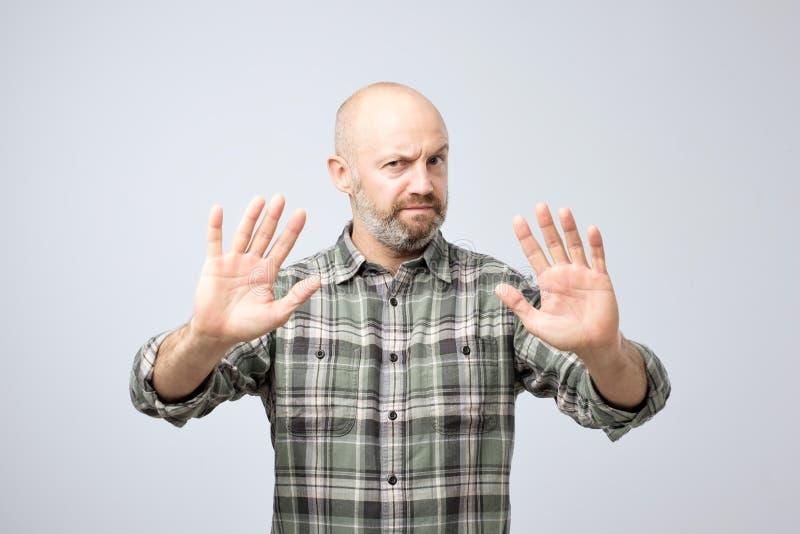 Homem maduro desagradado que recusa aceitar a ideia, esticando as mãos à câmera fotografia de stock