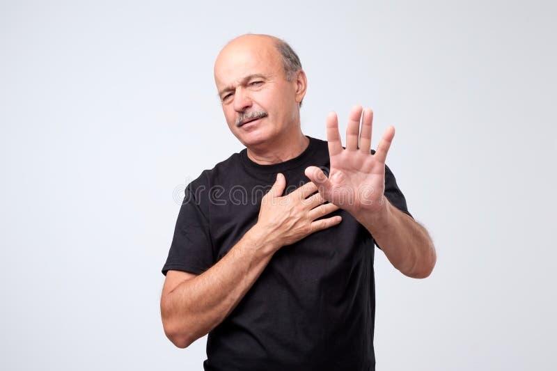 Homem maduro desagradado que recusa, esticando as mãos à câmera sobre o fundo cinzento foto de stock royalty free