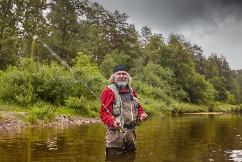 Homem maduro durante a pesca com mosca no rio imagem de stock royalty free