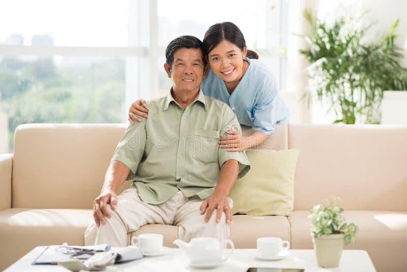 Homem maduro e seu doutor em casa imagens de stock