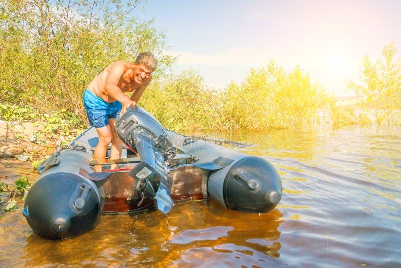 Homem maduro em um barco inflável com um motor no banco do rio em um dia ensolarado fotos de stock