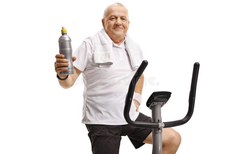 Homem maduro em uma bicicleta de exercício que guarda uma garrafa de água foto de stock