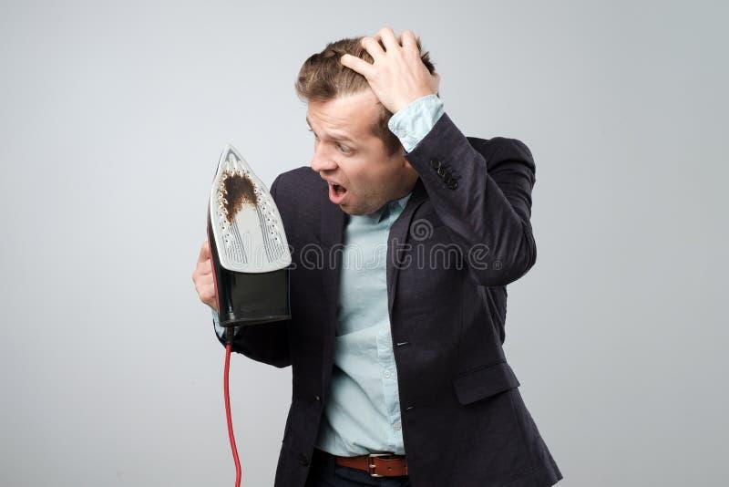Homem maduro europeu no terno que guarda o ferro bonde com o ponto queimado sujo fotos de stock royalty free