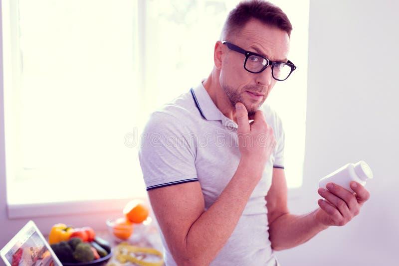 Homem maduro farpado considerável que sente curioso ao ler ingredientes das vitaminas fotos de stock