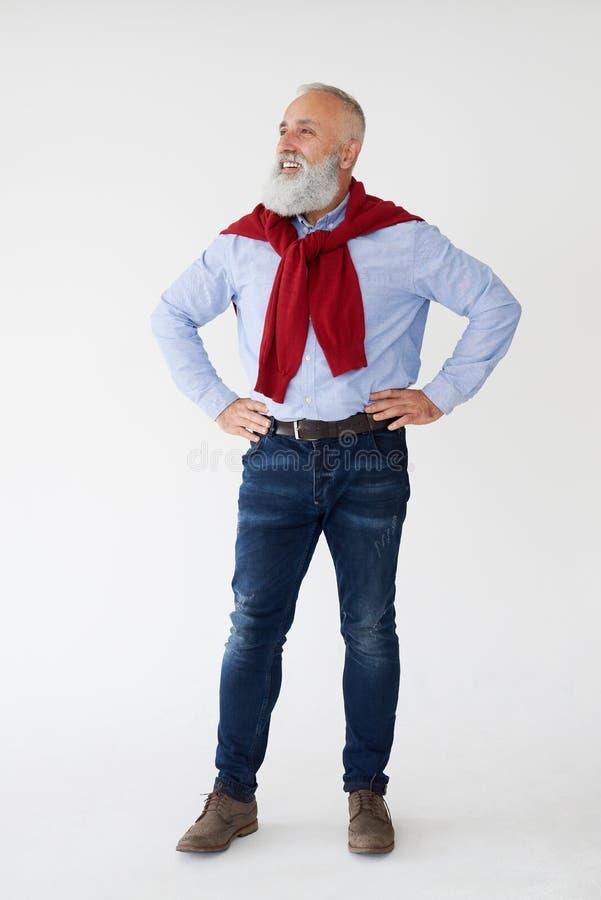 Homem maduro farpado positivo que guarda as mãos na cintura imagem de stock