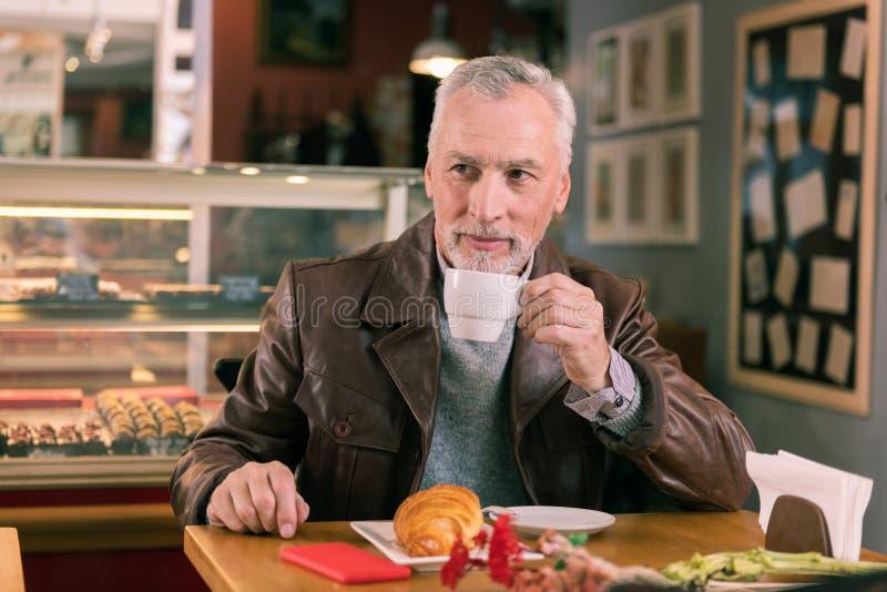Homem maduro farpado que aprecia o cheiro do croissant e do café frescos fotos de stock royalty free