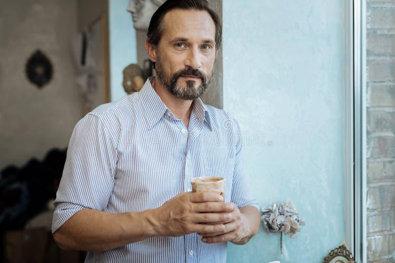 Homem maduro farpado que guarda o copo com chá quente foto de stock royalty free