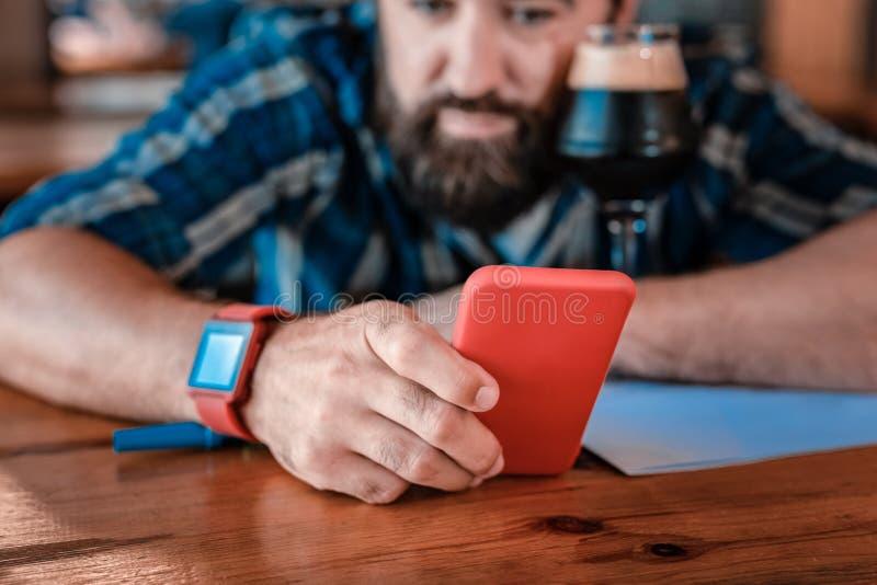 Homem maduro farpado que sente a mensagem de datilografia só seus amigos fotografia de stock