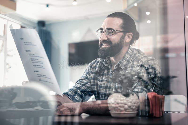 Homem maduro farpado que sorri ao escolher o prato para o jantar imagens de stock