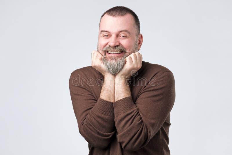 Homem maduro feliz com a barba que mant?m os bra?os perto do queixo foto de stock