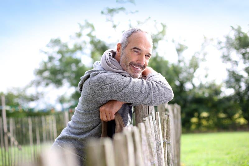 Homem maduro feliz no campo que inclina-se na cerca de madeira imagem de stock