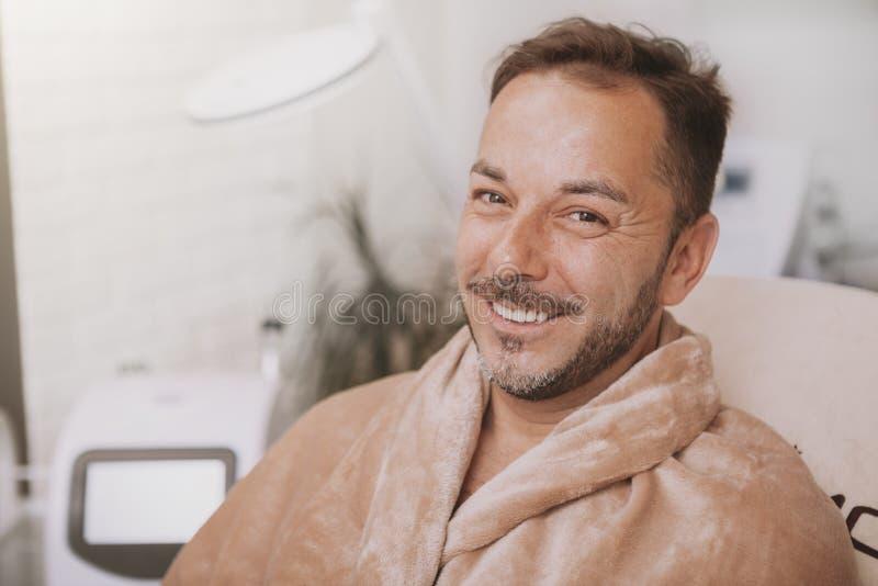 Homem maduro feliz que relaxa no centro dos termas imagens de stock