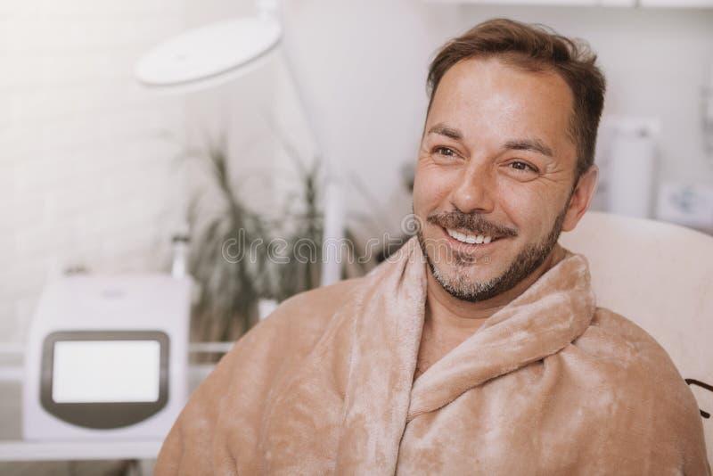 Homem maduro feliz que relaxa no centro dos termas fotografia de stock